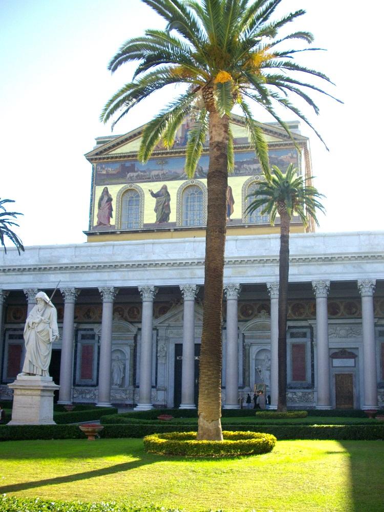 De binnenplaats van San Paolo fuori le Mura te Rome, met een beschilderde gevel, beeld van Paulus en palmboom
