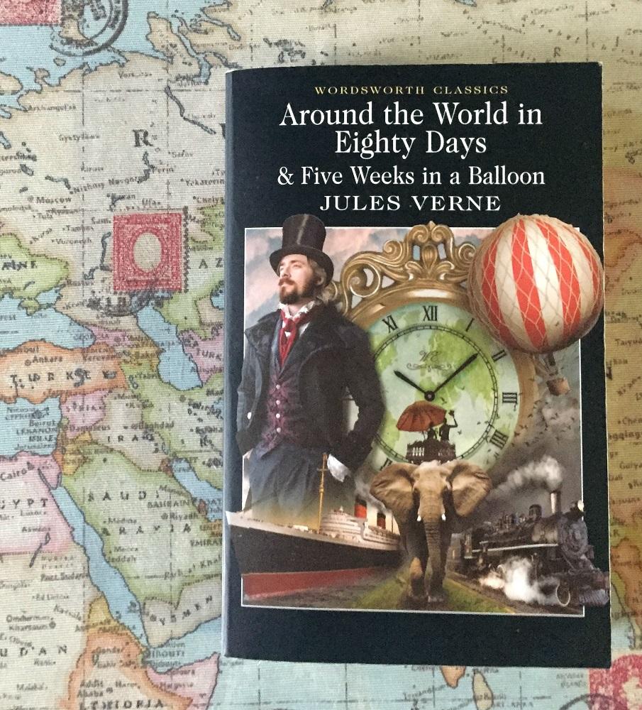 Het boek Around the world in eigthy days van Jules Verne op een wereldkaart