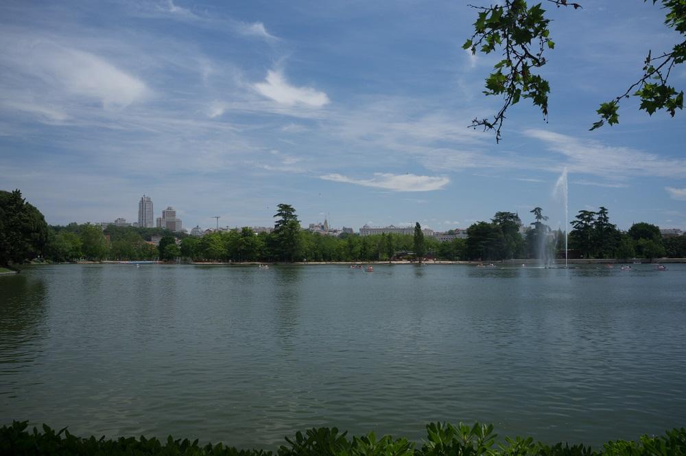 Het meer (lago) in het park Casa de Campo, met op de achtergrond de gebouwen van de stad, te Madrid