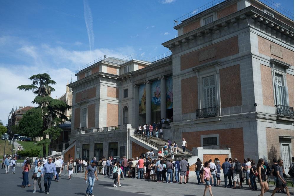Bezoekers voor het Prado museum staan voor de ingang in de rij, te Madrid
