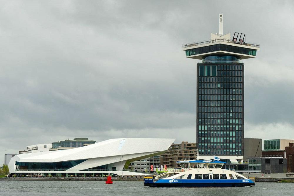Een pont vaart voor het EYE en de A'DAM Toren te Amsterdam-Noord