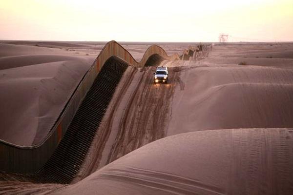 Een grenswacht rijdt langs het hek tussen Mexico en de VS in de woestijn
