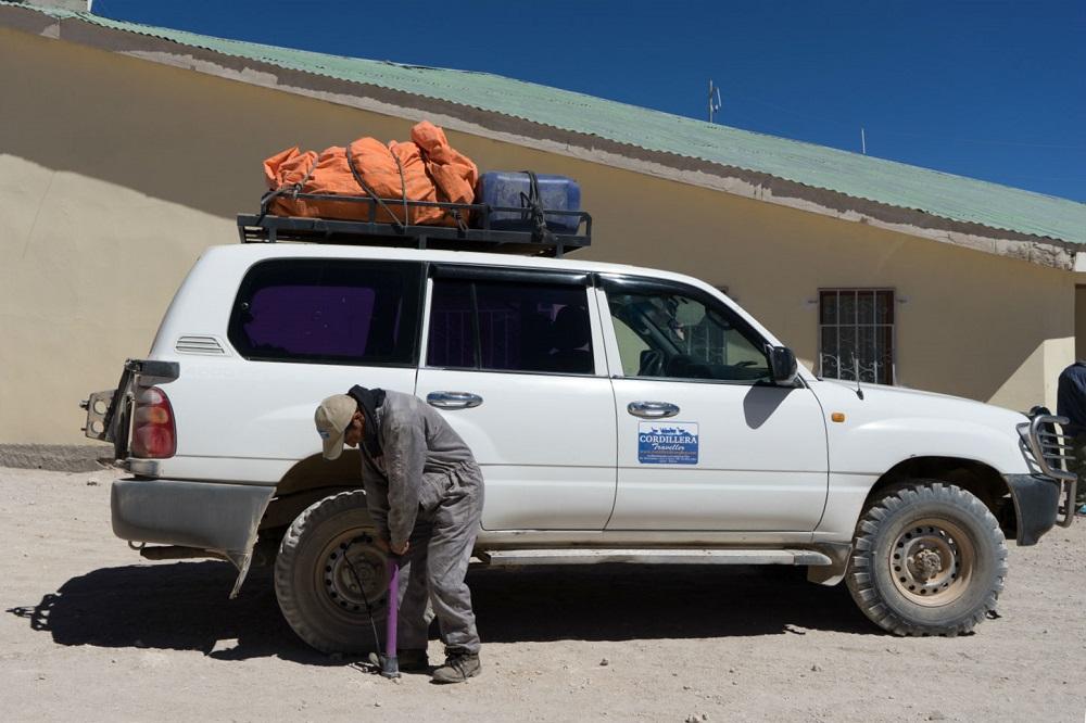 De achterband van de jeep wordt opgepompt met een fietspomp in Bolivia