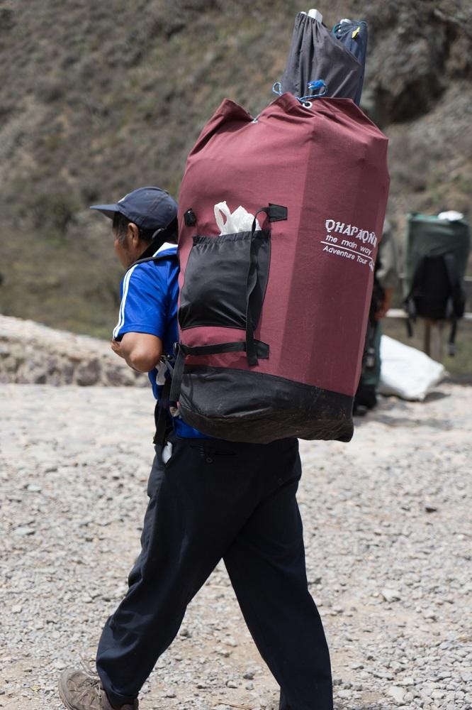Een porter met zijn bagage onderweg op de Inca Trail in Peru