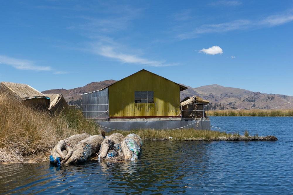 Afgedankte rietboten, opgevuld met plastic, bij de drijvende eilanden in het Titicaca-meer in Peru